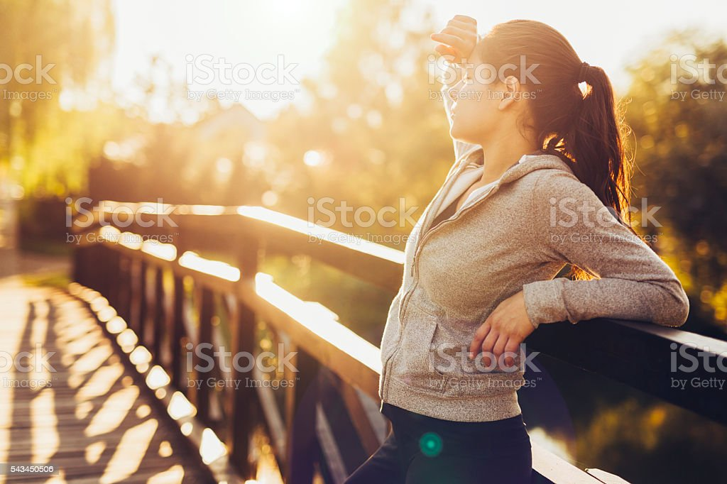 Beautiful woman resting after jogging outdoors stock photo