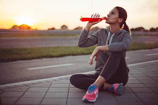 Beautiful woman resting after training and drinking energy drink stock photo