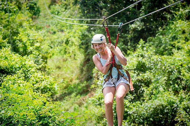 Beautiful woman riding a zip line in a lush tropical forest Beautiful happy woman riding a zip line in a lush tropical forest while on family vacation. Having fun and smiling with excitement zip line stock pictures, royalty-free photos & images