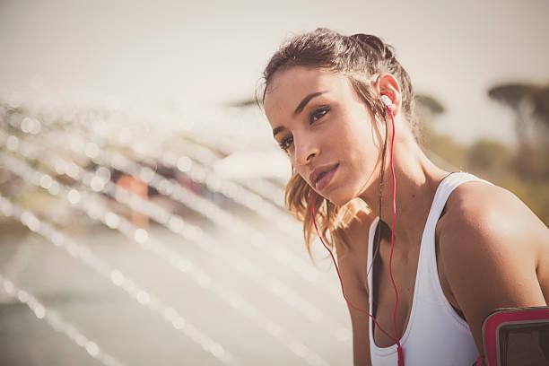 Beautiful woman runner listening to music on her smartphone stock photo