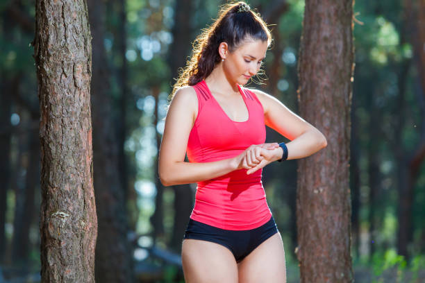 Beautiful woman runner looks at her fitness tracker getting ready for a run in the summer forest stock photo