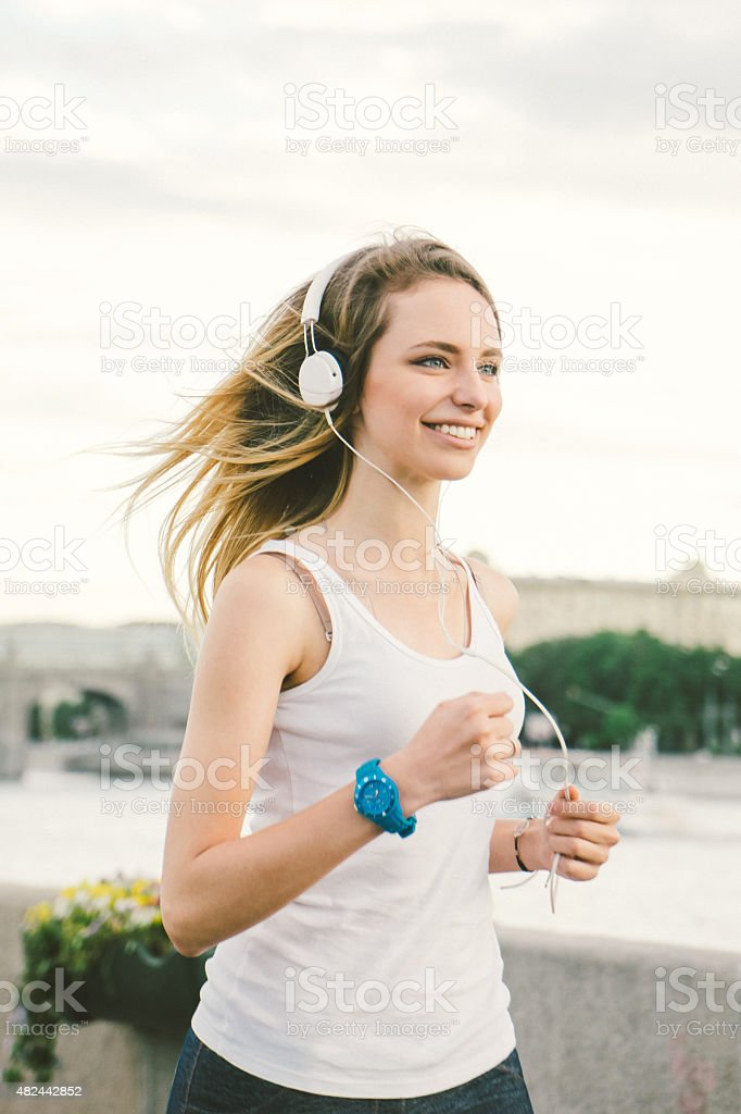 Beautiful Woman Running And Listening To Her Favorite Music stock photo