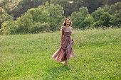 istock Beautiful woman running on the field 1287398466