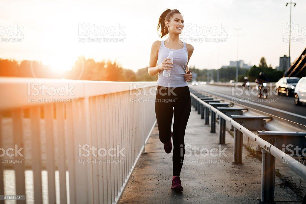 Beautiful woman running over bridge stock photo