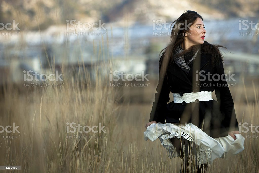 Beautiful woman running through a field of tall grass royalty-free stock photo