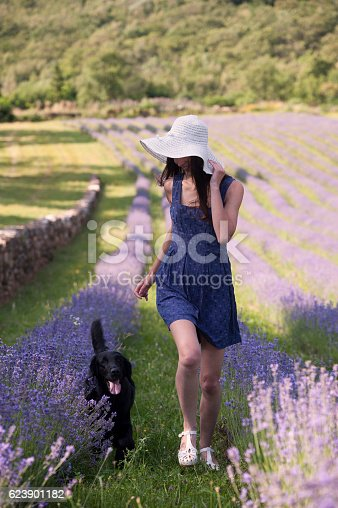 1054970060istockphoto Beautiful woman running with her dog in lavender field 623901182