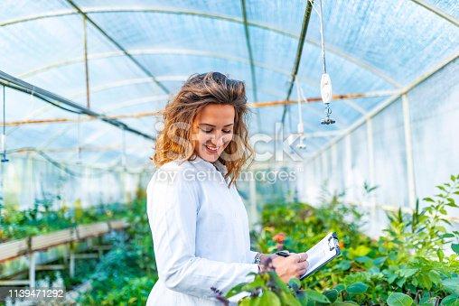 Female scientist inspects genetical varieties of plants. Happy female botanist studies plants.
