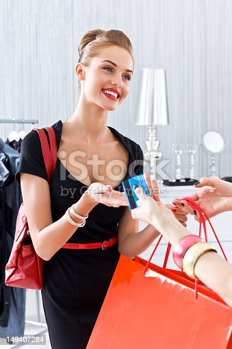 Beautiful young adult woman paying by credit card in luxury boutique.