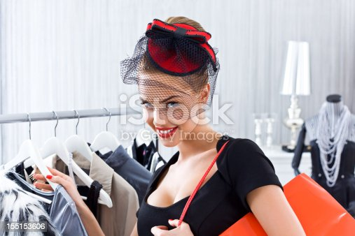 Beautiful and elegant young adult woman shopping in boutique, holding red shopping bag on her shoulder and smiling at camera.