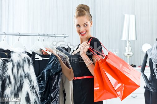 Beautiful and elegant young adult woman shopping in boutique, holding red shopping bag on her shoulder.