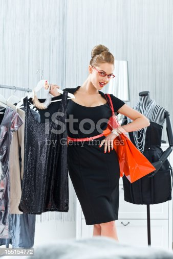 Beautiful and well-dressed young adult woman shopping in boutique, holding evening dress in her hand and looking at camera.