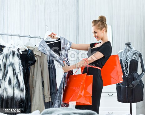 Beautiful young adult woman shopping in luxury boutique, looking at silver dress and smiling.