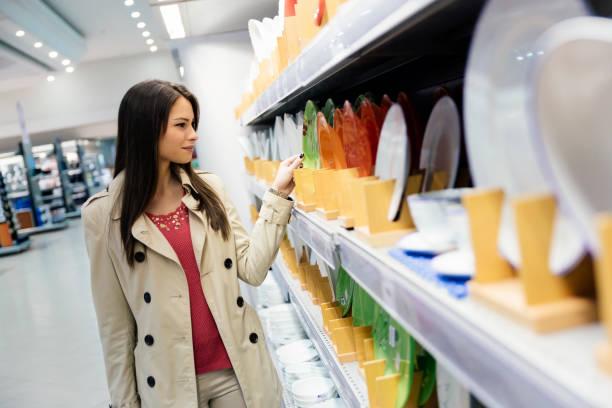 schöne frau geschirr im supermarkt einkaufen - teller kaufen stock-fotos und bilder