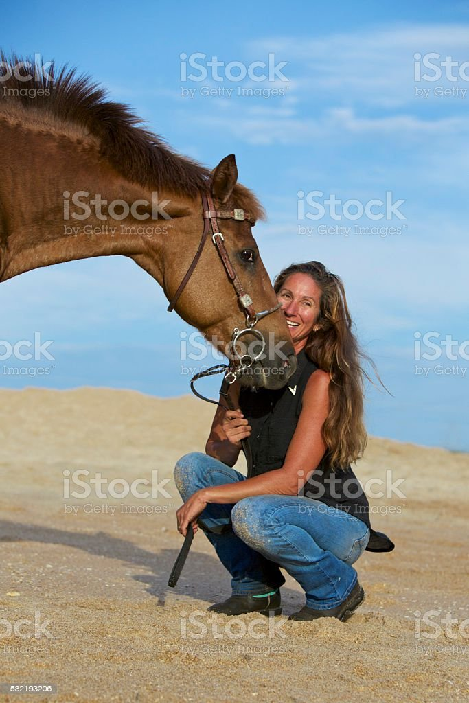 Beautiful woman showing affection to her horse. stock photo