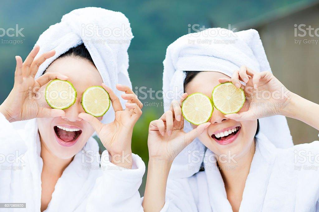 beautiful woman showing fresh lemon in spa stock photo
