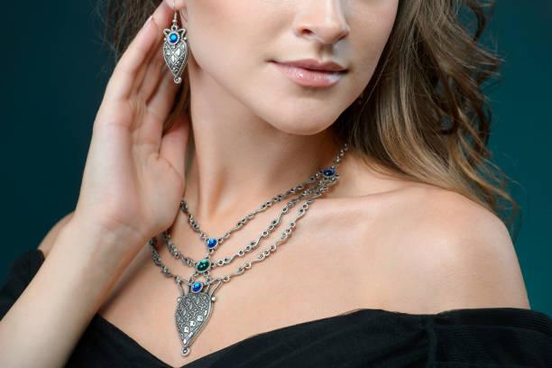 Mooie vrouw pronken haar sieraden in concept van de mode accessoires en sieraden geïsoleerd over donkere achtergrond dragen foto