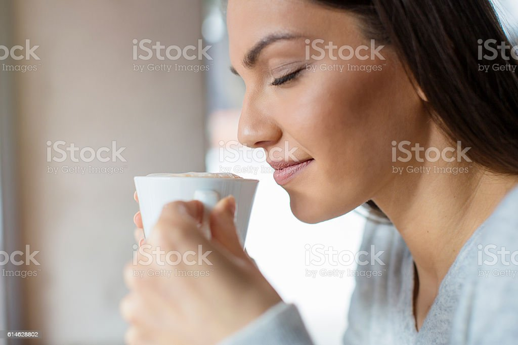 Beautiful woman sipping her coffee stock photo