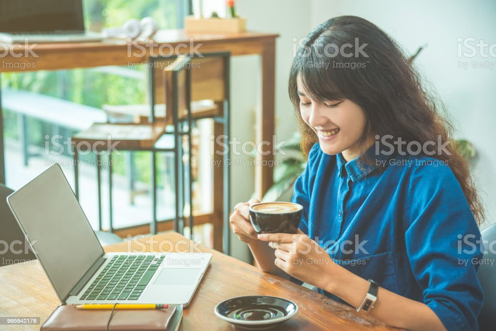 Beautiful woman sitting at home and using laptop computer stock photo