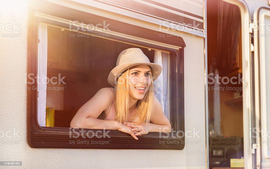 Beautiful woman sitting in a camper van stock photo