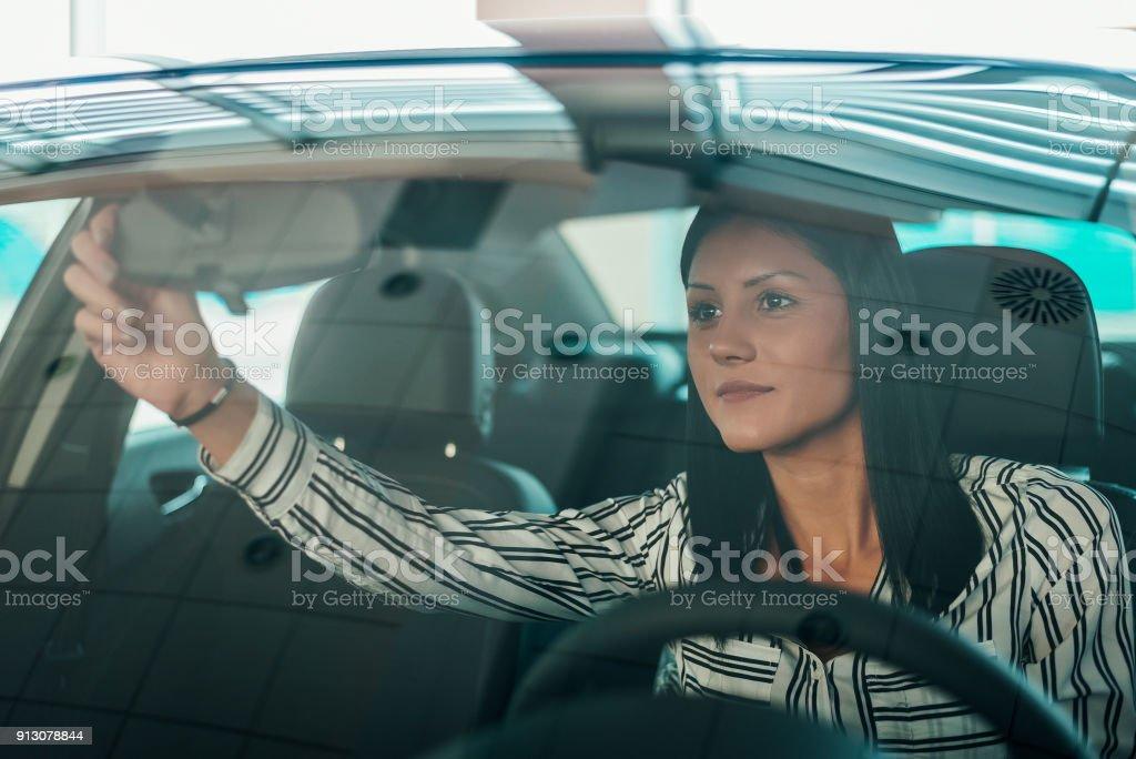 Mulher bonita sentada no carro, ajuste o espelho do carro. - foto de acervo