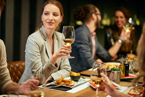 Beautiful woman sitting in restaurant with friends and holding glass of white wine.