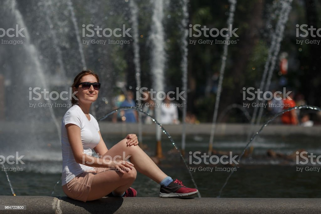 Beautiful woman sitting in sunglasses on the fountain background royalty-free stock photo