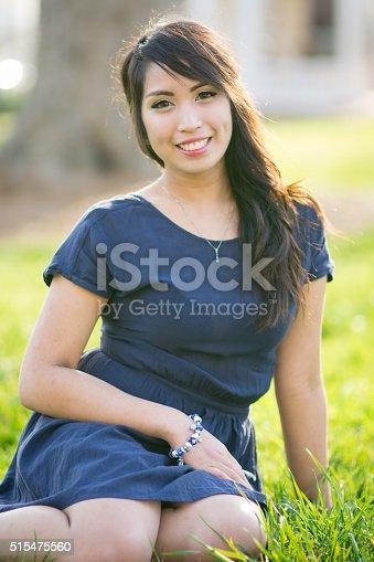 istock Beautiful Woman Sitting In The Grass 515475560