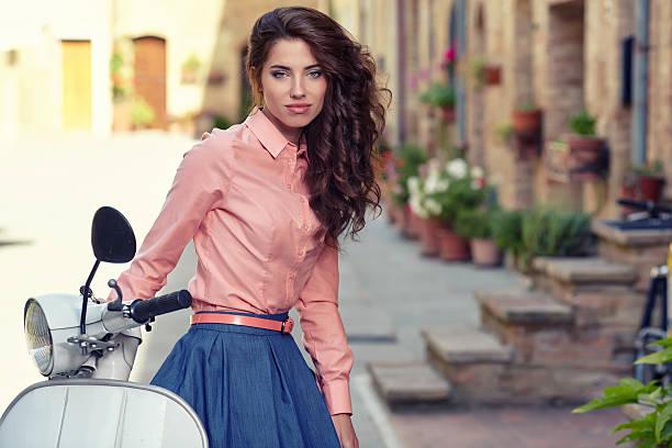 아름다운 여인 앉아 있는 이탈리어어 스쿠터를 타세요. 스톡 사진