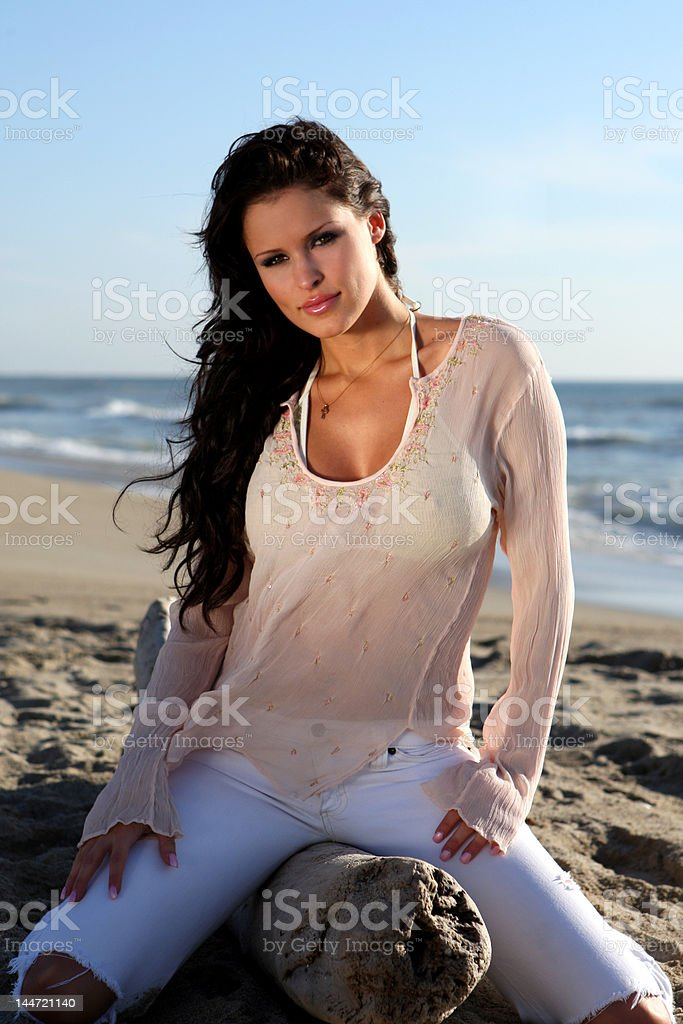 Beautiful woman sitting on a log at the beach royalty-free stock photo