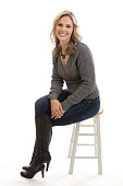 Full length portrait of a beautiful mid 30s blond woman sitting on a stool wearing sweater and blue jeans isolated on white background