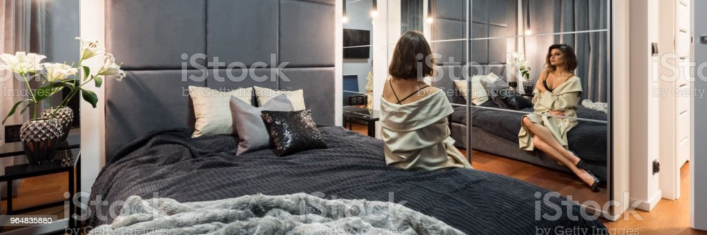 Beautiful woman sitting on bed royalty-free stock photo
