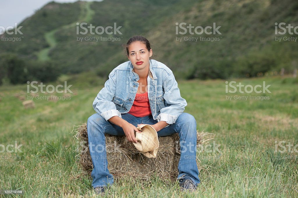 Beautiful woman sitting on hay in a field stock photo