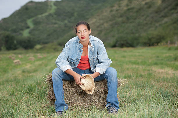 beautiful woman sitting on hay in a field - kellyjhall stock pictures, royalty-free photos & images