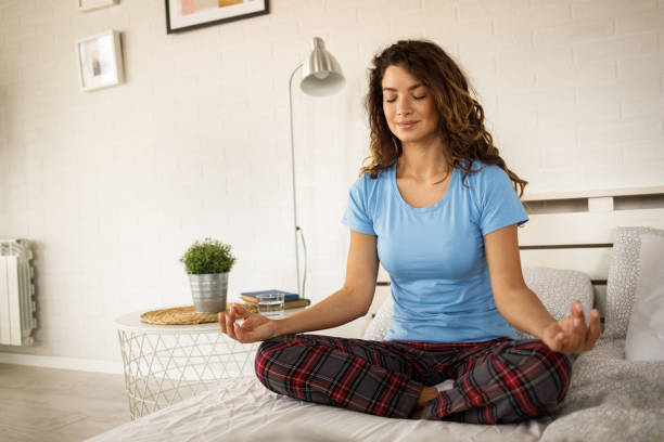 Beautiful woman sitting on her bed and meditating alone during the morning at home stock photo