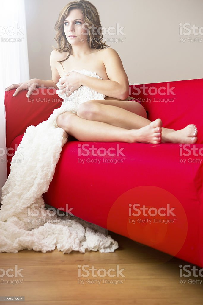 Beautiful woman sitting on red couch royalty-free stock photo