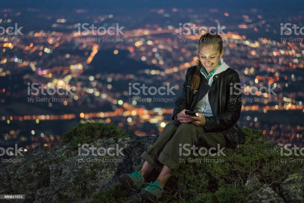 Beautiful woman sitting on the mountain peak and browsing on her phone. stock photo
