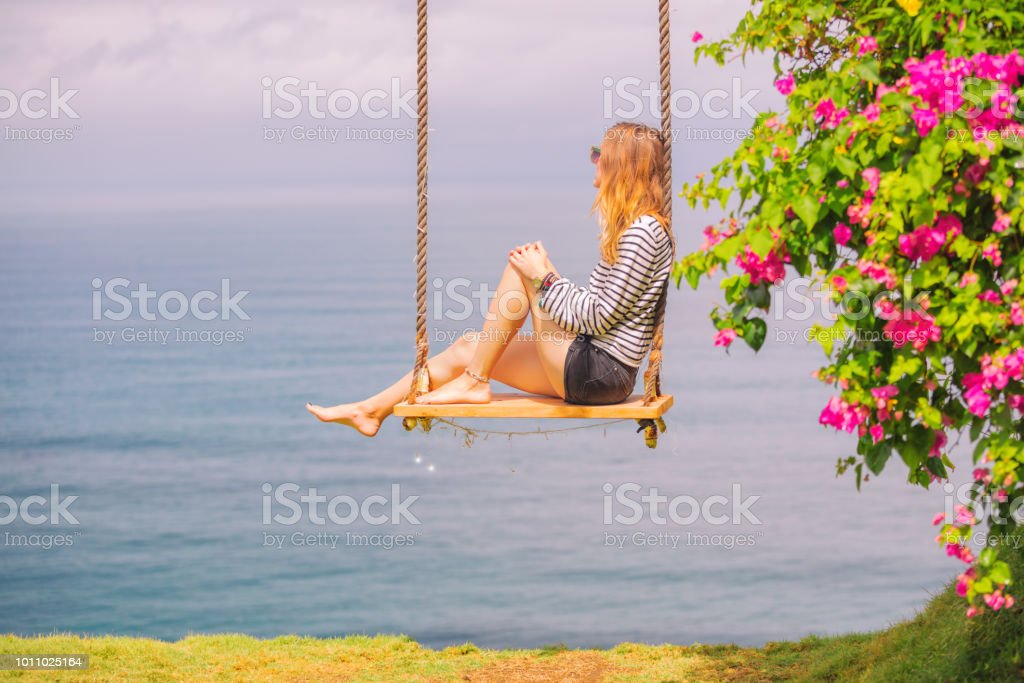 Beautiful woman sitting on the wooden swing and enjoying the view on the ocean/sea. stock photo