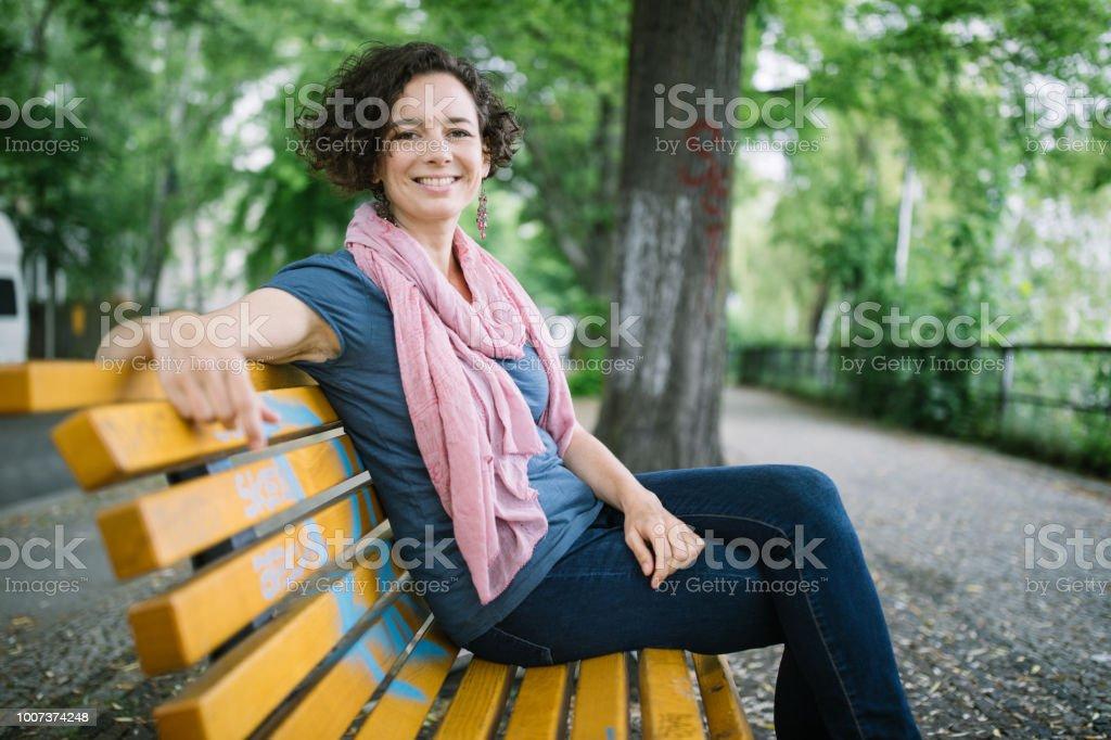 Beautiful woman sitting outside on bench stock photo