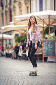 Beautiful young woman skateboarding on the city street. Cool young woman riding skateboard on the road.