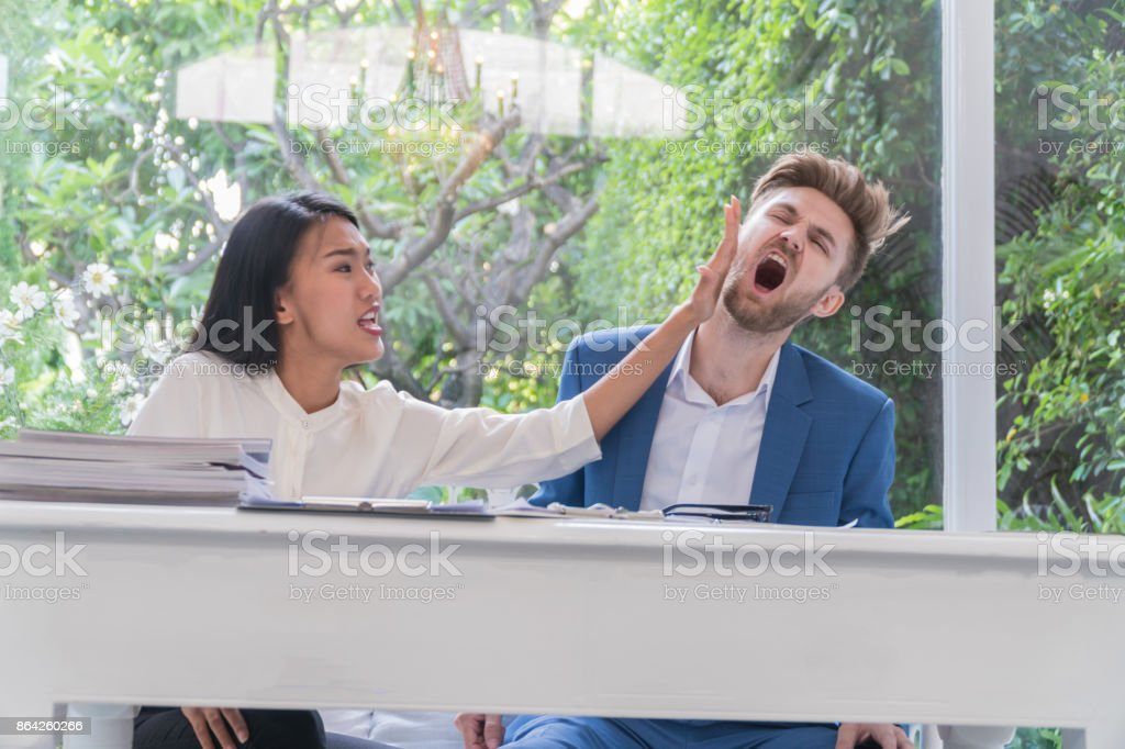 Beautiful woman slapped the handsome young man at living room. royalty-free stock photo