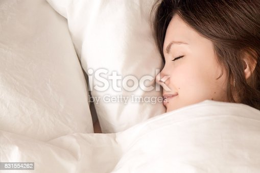 istock Beautiful woman sleeping in cozy bed, closeup headshot top view 831554262