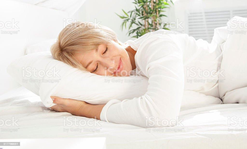 Linda mulher dormindo na cama branca - foto de acervo