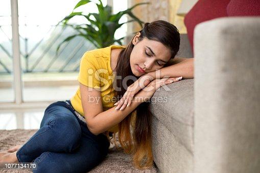 istock Beautiful woman sleeping on sofa 1077134170