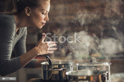 Young woman smelling soup that she is preparing for lunch.