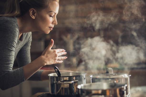 beautiful woman smelling delicious lunch she is preparing in the kitchen. - annusare foto e immagini stock