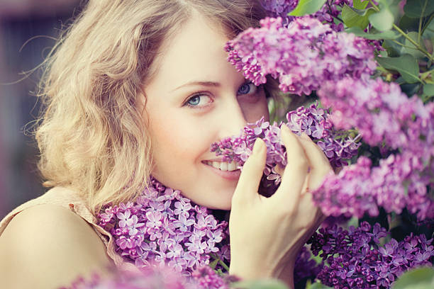 Beautiful woman smelling lilac flowers stock photo