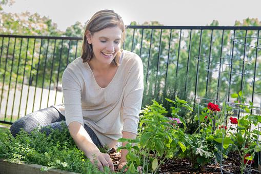 Beautiful woman smiles while gardening