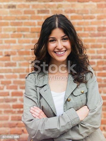 istock Beautiful woman smiling in the street 624567396