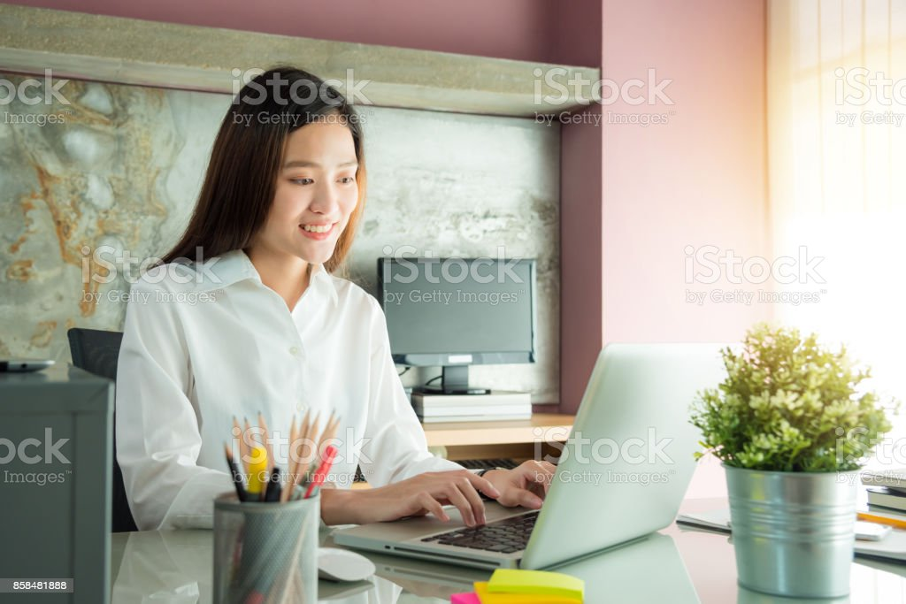 beautiful woman smiling while working in office stock photo