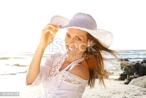 istock Beautiful woman smiling with hat at the beach 511545178